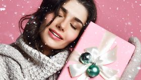 Smiling Young girl in sweater and mittens holding gift box stock photo