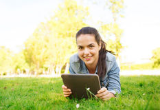 Smiling young girl tablet pc lying on grass Royalty Free Stock Image