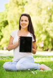 Smiling young girl with tablet pc sitting on grass Royalty Free Stock Images