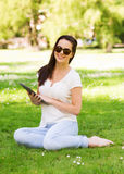 Smiling young girl with tablet pc sitting on grass Stock Image