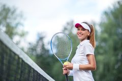 Smiling young girl with a tennis racket stock images