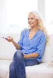 Smiling young girl with tv remote control at home Royalty Free Stock Photos