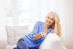 Smiling young girl with tv remote control at home Royalty Free Stock Image