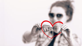 Smiling young girl with  two sunglasses in the form of hearts. Smiling young girl with two sunglasses in the form of hearts in black white and red heart symbol Stock Images