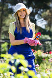 Smiling young girl  in uniform at yard gardening Stock Image