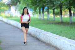 Smiling young girl walking in the park gait stock photo