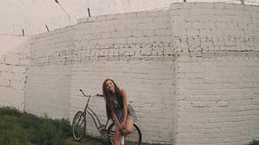 Smiling young girl weaving hand, retro color shot. Young woman posing near bycicle leaning wall. Retro color stock video footage