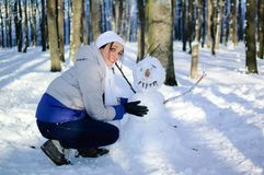 Smiling young girl in white hat and scarf hugging funny snowman in the park during a sunny day. Blue sky and frosty Stock Photography