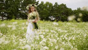 Smiling young girl in wreath with flowers bouquet standing on flowering field. Beautiful girl posing front camera on. Blooming meadow at summer windy day stock footage