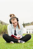 Smiling young girl writing on journal while sitting on grass Royalty Free Stock Photography
