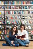 Smiling young girl and young man sitting on the floor in the lib Stock Photo