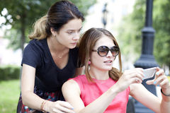 Smiling young girls with cell phone sitting on a bench in a park Stock Photo
