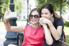 Smiling young girls with cell phone sitting on a bench in a park Royalty Free Stock Photos