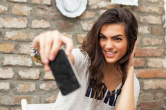 Smiling young girls is taking selfie. At cafe Royalty Free Stock Image