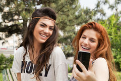 Smiling young girls taking selfie. In a park Royalty Free Stock Image