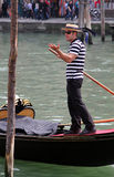 Smiling young gondolier  in traditional dress on his gondola on the Grand Canal Royalty Free Stock Photos