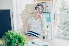 Smiling young gorgeous asian girl secretary is drinking tea at the break in office and talk on the pda in nice work place, wearin 库存照片