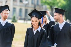 smiling young graduated students in capes royalty free stock photo