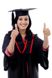 Smiling young graduation student making thumbsup gesture Stock Images