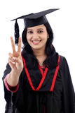 Smiling young graduation student making thumbsup gesture Stock Photography