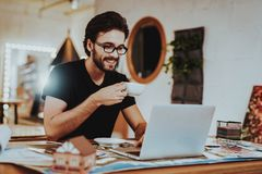 Smiling Young Graphic Designer Has Coffee Break. Portrait of Happy Professional Illustrator Working at Project Indoors Sitting at Workplace Drinks Tea royalty free stock photography