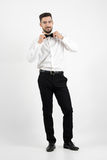 Smiling young groom adjusting bow tie looking at camera Stock Photos