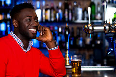 Smiling young guy in bar looking at something Stock Photography