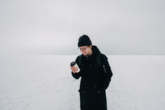 Smiling young guy hipster in black on the white snow-covered frozen pond with a cup of coffee Royalty Free Stock Image