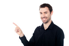 Smiling young guy pointing at something Royalty Free Stock Image