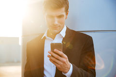 Smiling young handsome businessman using mobile phone outdoors Stock Photography