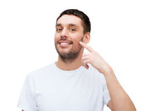 Smiling young handsome man pointing to cheek Stock Image