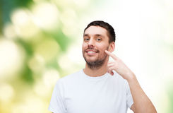 Smiling young handsome man pointing to cheek Royalty Free Stock Images