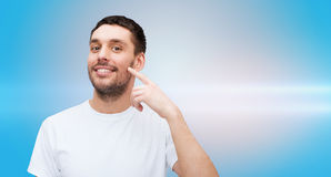 Smiling young handsome man pointing to cheek Royalty Free Stock Photo