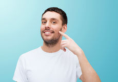 Smiling young handsome man pointing to cheek Stock Images