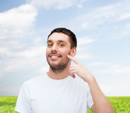 Smiling young handsome man pointing to cheek Stock Photo