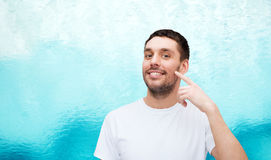 Smiling young handsome man pointing to cheek Royalty Free Stock Photography
