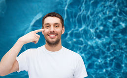 Smiling young handsome man pointing to eyes Stock Image