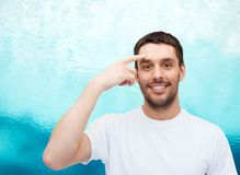 Smiling young handsome man pointing to forehead Stock Photo