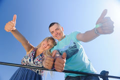 Smiling young happy couple showing thumbs up. Happy young couple with his thump up having fun in nature on blue clear sky background Stock Image