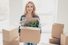 Smiling young happy woman moving new place of leaving and holdin royalty free stock image