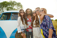 Smiling young hippie friends over minivan car Royalty Free Stock Photography