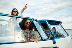 Smiling young hippie friends over minivan car Royalty Free Stock Photos