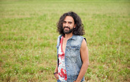 Smiling young hippie man on green field Royalty Free Stock Images