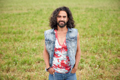 Smiling young hippie man on green field Royalty Free Stock Image