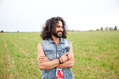 Smiling young hippie man on green field Stock Photo
