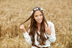 Smiling young hippie woman on cereal field. Nature, summer, youth culture and people concept - smiling young hippie woman wearing flower wreath on cereal field Stock Images