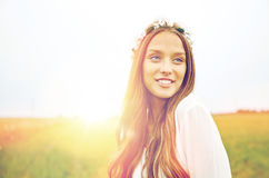 Smiling young hippie woman on cereal field. Nature, summer, youth culture and people concept - smiling young hippie woman wearing flower wreath on cereal field Stock Photography