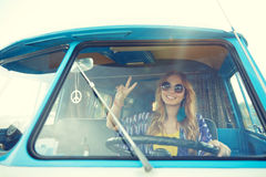 Smiling young hippie woman driving minivan car. Summer holidays, road trip, vacation, travel and people concept - smiling young hippie woman driving minivan car Stock Photography