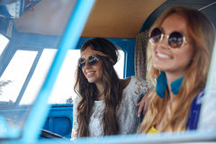 Smiling young hippie women driving minivan car Stock Images