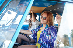 Smiling young hippie women driving minivan car Royalty Free Stock Images
